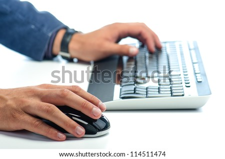 Man's hands working with computer mouse and  computer keyboard against white background - stock photo
