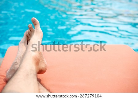 Man 's leg relax on pool bed - stock photo