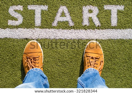 Man's legs behind the white line from above with START sign - stock photo
