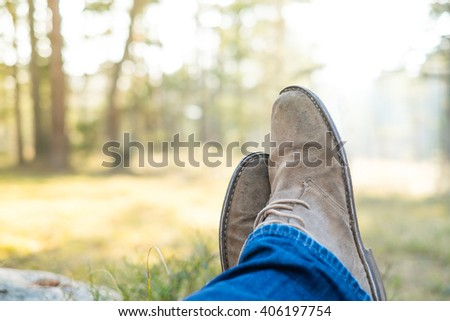 Man's legs during the rest after the long trip - stock photo