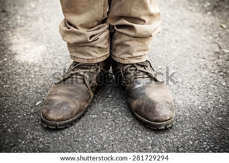 man's legs in  brown jeans and  brown leather shoes - stock photo