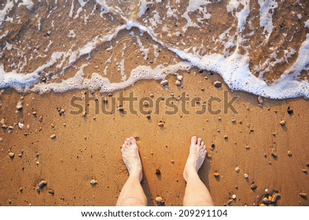 Man's legs on the sand beach and sea waves at sunset - stock photo