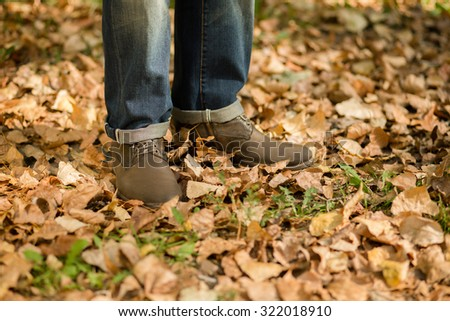 Man's legs standing on multi-coloured leaves in autumn park. Beautiful season and man are nice idea for it enjoying.