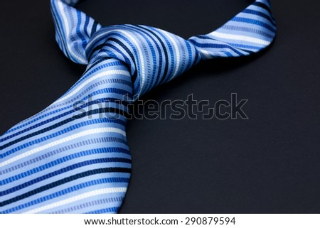 Man's neck tie laying on a black background - stock photo