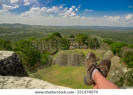 man's shoes overlooking xunantunich maya site ruins in belize caribbean - stock photo