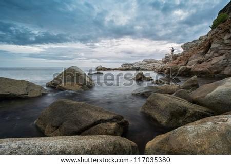 Man's silhouette  on rocky seashore - stock photo