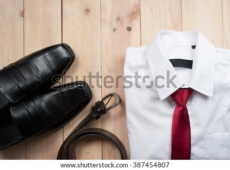 Man's style accessories,shirt with a bright tie, shoes and a belt on wooden background