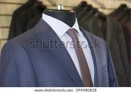 Man's suit: jacket, shirt & a tie on background of jackets inside of shopping mall. Business style. Elegant clothes. Men fashion industry. Stylish blue jacket, white cotton shirt. Representative suit