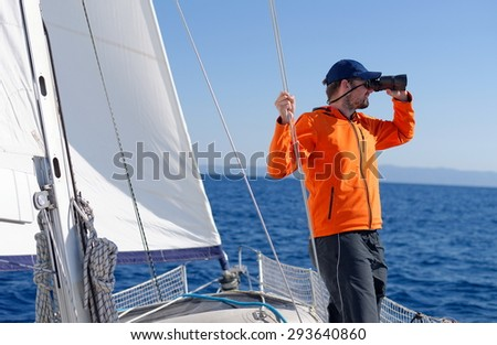 Man sailing with sails out on a sunny day - stock photo