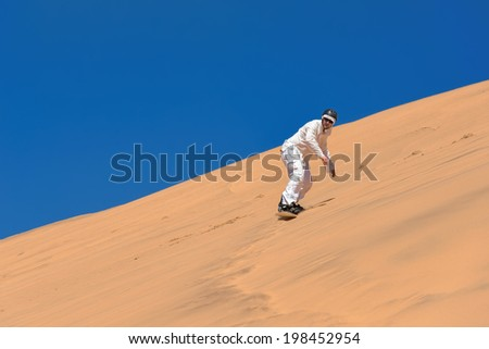 Man sand-boarding in Swakopmund, Namibia - stock photo