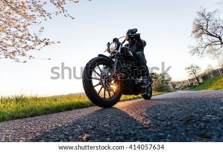 Man sat on motorcycle on the road during sunrise. - stock photo