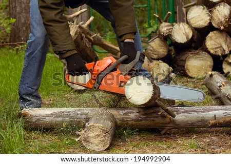 Man sawing a log in his back yard. Toned in warm color - stock photo