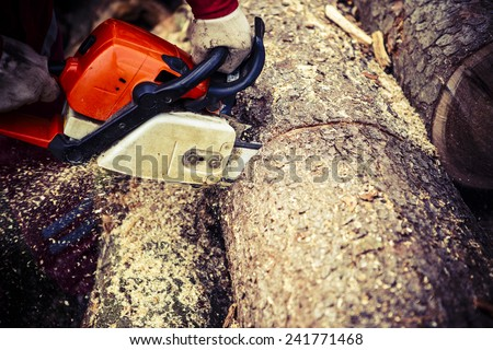Man sawing a log in his back yard with orange chain saw - stock photo
