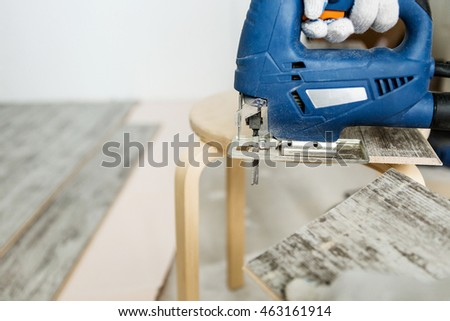 Man sawing laminate. Man is repairing the floor in the house, laminate flooring in the style of old boards.