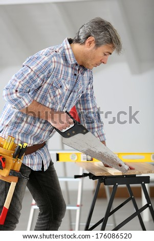 Man sawing wood for home renovation