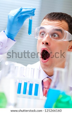 man scientist holding a test tube with liquid - stock photo