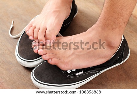 Man scratching his athlete's foot.Close up. - stock photo