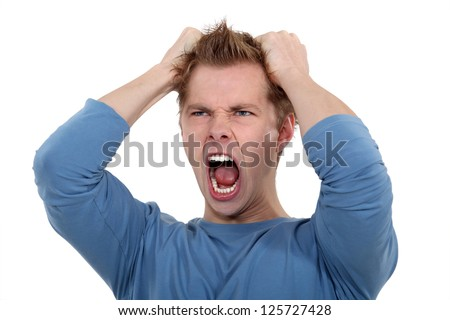 Man screaming and pulling his hair - stock photo