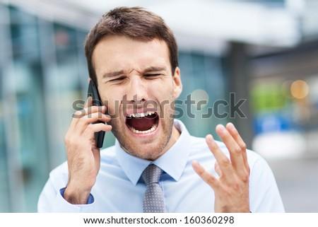 Man screaming at phone - stock photo