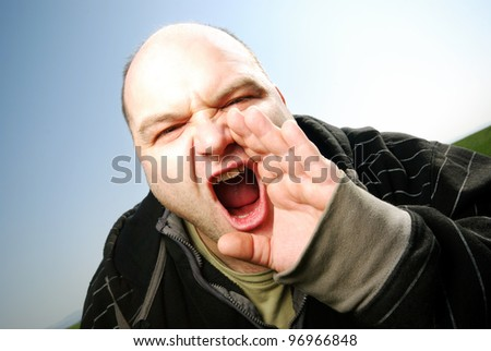 man screaming in front of blue sky - stock photo