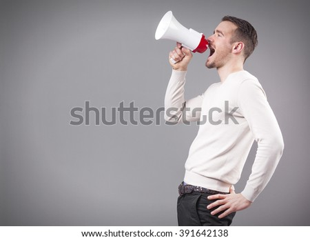 Man screaming with a megaphone on grey background - stock photo
