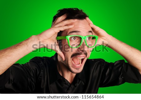 man screaming with green eyeglasses on green background