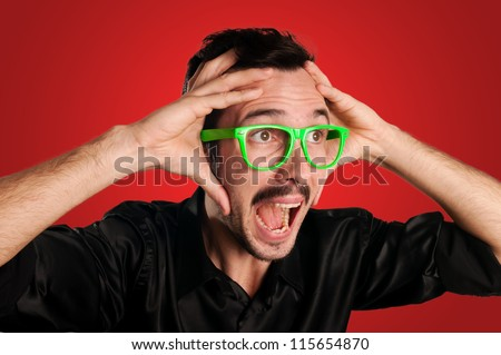 man screaming with green eyeglasses on red background