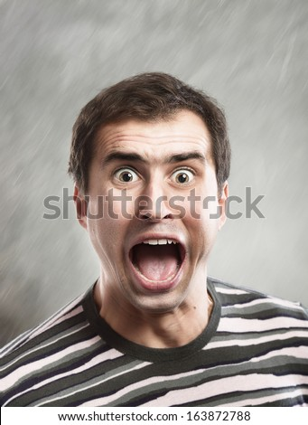 Man screams opening the mouth, close-up shot, abstract gray background  - stock photo