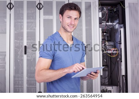 Man scrolling through tablet pc against data center - stock photo
