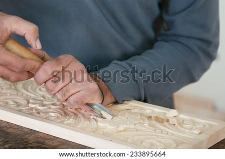 Man Sculptor  sculpting wood to create a wooden flora design. - stock photo