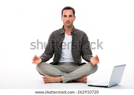 Man seated on the floor looking at the camera and practicing yoga with laptop next to him - stock photo