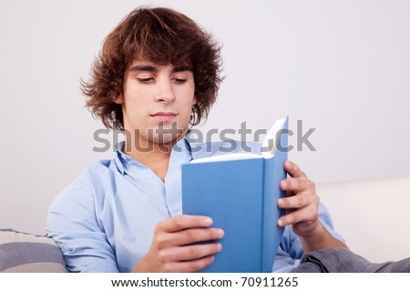 man seated reading a book on couch