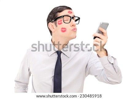 Man sending a kiss through a cell phone isolated on white background - stock photo