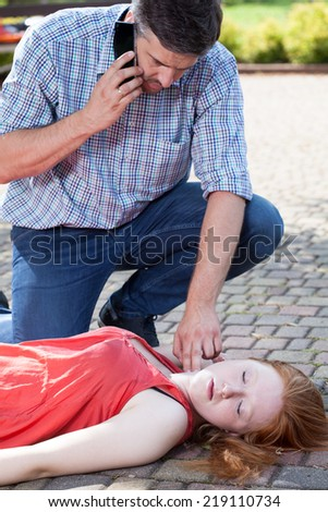 Man sending for an ambulance and taking girl's pulse