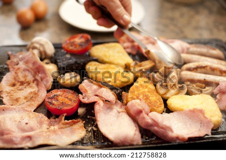 Man serving a hearty cooked breakfast warming on the griddle with bacon, tomato, hash browns, mushrooms and sausages - stock photo