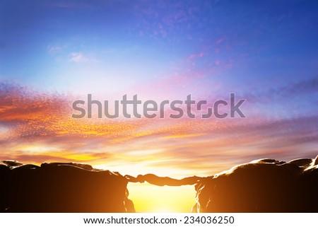 Man serving as a bridge over precipice between two mountains. Sunset, business conceptual - stock photo