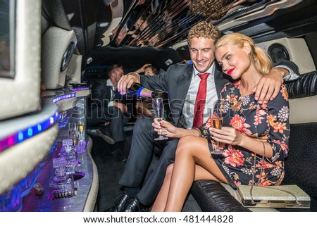 Man Serving Champagne For Girlfriend In Limousine