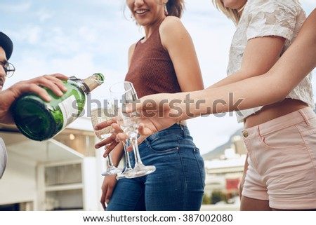 Man serving champagne to friends during party. Cropped shot with focus on hands and champagne glasses. Young people having champagne at party outdoors. - stock photo