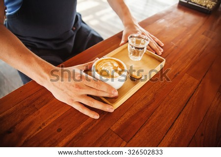 man serving latte on a wooden table