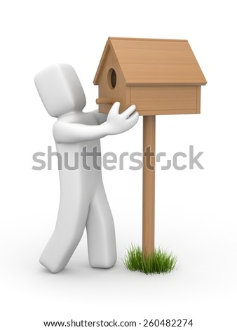 Man sets birdhouse - stock photo