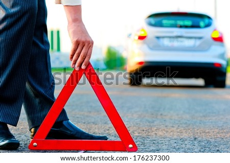 man sets the warning triangle - stock photo