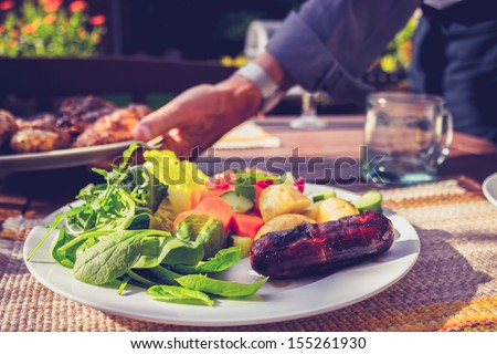 Man setting table at outdoors barbecue - stock photo