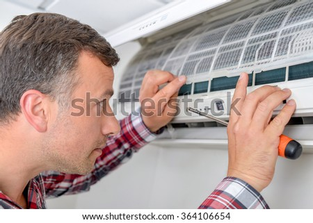 Man setting up an air conditioning unit - stock photo