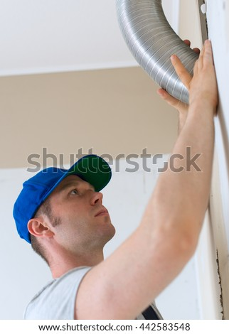Man setting up ventilation system indoors. - stock photo