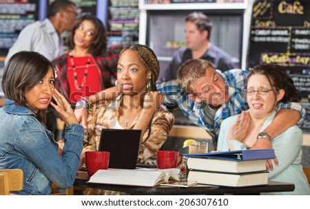 Man sexually harassing diverse group of students in cafe - stock photo