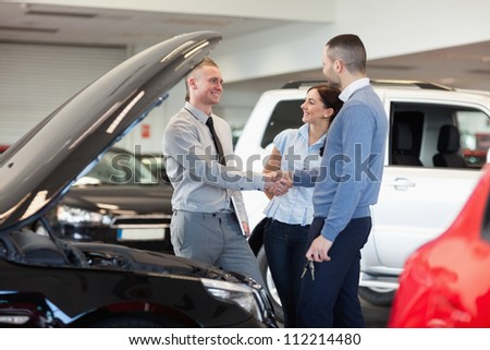 Man shaking hand of a car dealer in front of a car in a car shop