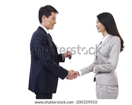 man shaking hand with woman while handing her a car key. - stock photo