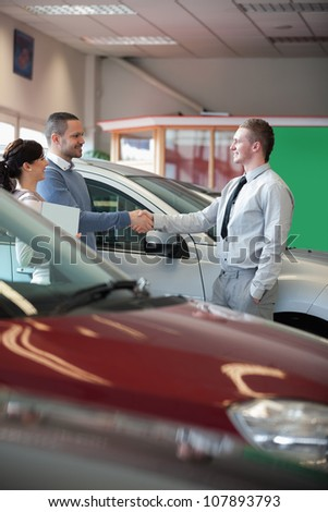 Man shaking the hand of a salesman in a car shop