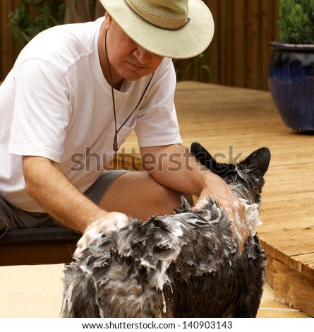 man shampoos dog outdoors