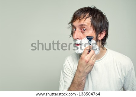 Man shaving in the bathroom, looking at the mirror.